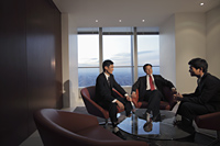 Three businessmen talking in office - Alex Mares-Manton