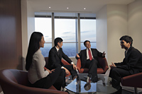 Four people having a meeting in an office - Alex Mares-Manton