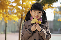 Young girl holding Autumn leaves outdoors - Alex Mares-Manton