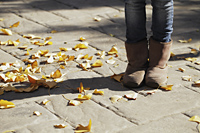 Cropped shot of young girl wearing boots with Autumn leaves on the ground - Alex Mares-Manton