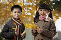Young boy and girl holding Autumn leaves outdoor - Alex Mares-Manton