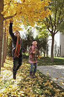 Young boy and girl playing in the Autumn leaves outdoors - Alex Mares-Manton