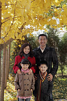 Family of four wearing coats standing under a tree with yellow leaves - Alex Mares-Manton