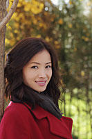 Head shot of young woman in a red coat under a tree - Alex Mares-Manton