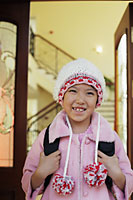 Young girl leaving her house in knitted hat and pink coat - Alex Mares-Manton