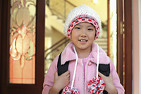 Young girl leaving her home in knitted cap and pink coat - Alex Mares-Manton