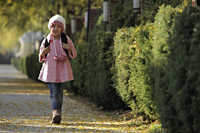 Young girl walking down street wearing pink coat and hat and backpack - Alex Mares-Manton