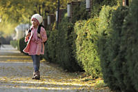 Young girl walking down sidewalk wearing pink coat, hat and backpack - Alex Mares-Manton