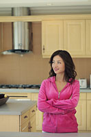 Young woman wearing pink smiling in her kitchen - Alex Mares-Manton