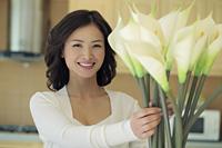 Young woman arranging flowers - Alex Mares-Manton