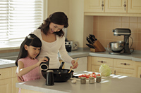Mother and daughter making food together - Alex Mares-Manton