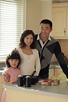 Young family cooking together in kitchen - Alex Mares-Manton