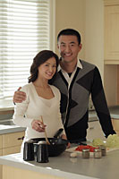 Young couple cooking together in the kitchen - Alex Mares-Manton