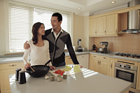 Young couple cooking together in their kitchen - Alex Mares-Manton