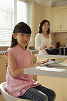 Mother watching her young daughter play on a digital tablet as she cooks - Alex Mares-Manton