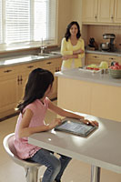 Mother watching her daughter play on a digital tablet as she cooks - Alex Mares-Manton