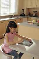 Young girl plays on a digital tablet computer in the kitchen - Alex Mares-Manton