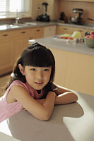 Young girl sitting at the kitchen counter - Alex Mares-Manton