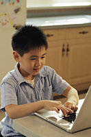 Young boy playing on a lap top computer in the kitchen - Alex Mares-Manton