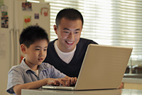 Father and son working on laptop computer together in kitchen - Alex Mares-Manton