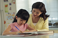 Mother helping her daughter with her homework - Alex Mares-Manton
