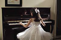 Rear view of young girl playing piano in white dress - Alex Mares-Manton