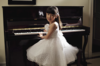 Young girl playing piano in white dress - Alex Mares-Manton