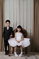 Young boy and girl dressed up in nice clothes smiling - Alex Mares-Manton