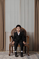 Young boy wearing suit sitting on nice chair - Alex Mares-Manton