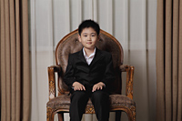 Young boy dressed up in suit sitting on a nice chair - Alex Mares-Manton