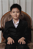 Young boy wearing a suit sitting on a chair - Alex Mares-Manton