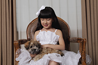 Young girl dressed up in white dress holding a puppy - Alex Mares-Manton