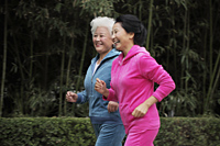 Two older women jogging together - Alex Mares-Manton