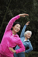 Two older woman stretching together outdoors - Alex Mares-Manton