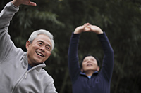 Two older men stretching outdoors - Alex Mares-Manton