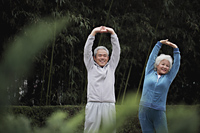 Senior man and woman stretching together outdoors - Alex Mares-Manton