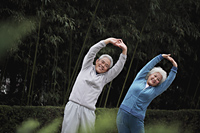 Older man and woman stretching together outdoors - Alex Mares-Manton