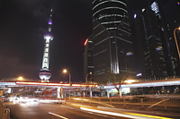 Shanghai streets at night with The Oriental Pearl Tower in background - Alex Mares-Manton