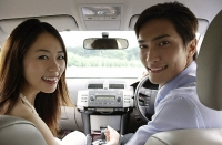 Couple driving in car, looking in back seat - Asia Images Group