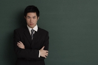 Businessman standing against black wall with arms crossed - Asia Images Group