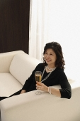 elegant woman sitting on couch with glass of champagne - Asia Images Group