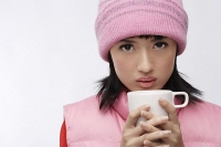 Young woman in pink hat and vest with coffee cup - Asia Images Group