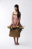 Young woman holding straw bag full of flowers - Asia Images Group