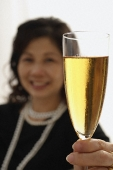 Woman holding up glass of champagne - Asia Images Group