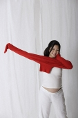 Pregnant woman putting on red sweater - Asia Images Group