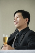 Man enjoying glass of champagne - Asia Images Group