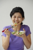 Woman eating green salad - Asia Images Group