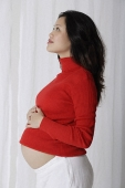 Profile of pregnant woman with hands on stomach - Asia Images Group