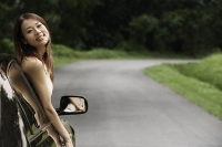 Woman hanging out car window - Asia Images Group