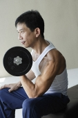 Profile of man lifting arm weights - Asia Images Group